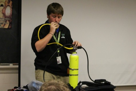 Trinity sophomore Nick Craven shows the communications skills class how to use SCUBA equipment.