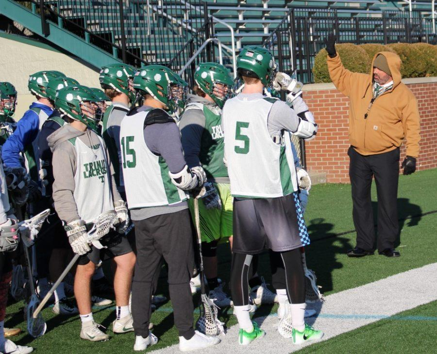 Trinity lacrosse head coach Pete Schroeder talks with his team during practice.