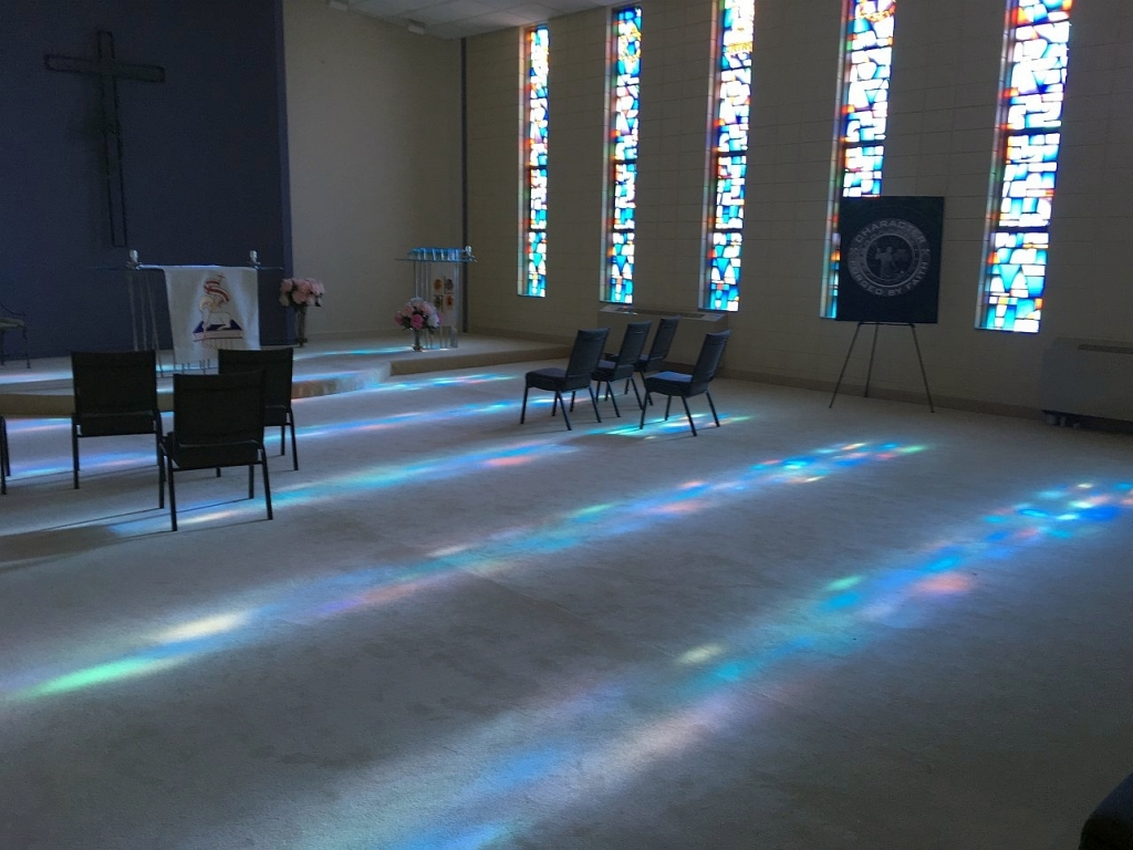 Stained-glass+rainbows+were+created+as+the+evening+light+came+through+in+Trinity%27s+chapel.+