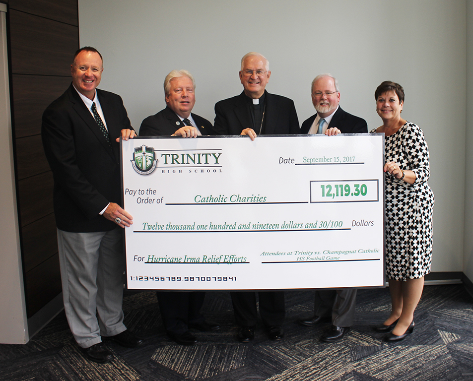 Trinity Athletic Director Rob Saxton and Trinity President Dr. Rob Mullen presented a check for $12,119.30 to Catholic Charities, represented by Archbishop Joseph E. Kurtz, Chancellor Dr. Brian Reynolds and Superintendent Leisa Schulz.