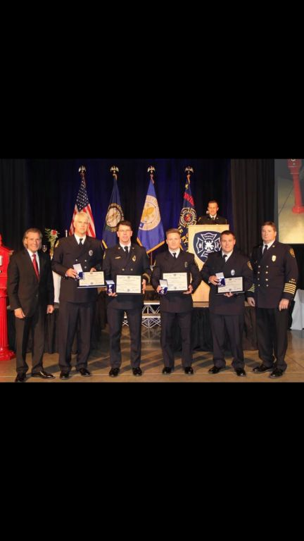 Trinity+2012+alumnus++Daniel+Hogg%2C+a+firefighter+standing+second+from+the+right+next+to+Chief+Greg+Frederick%2C+was+honored+for+valor.