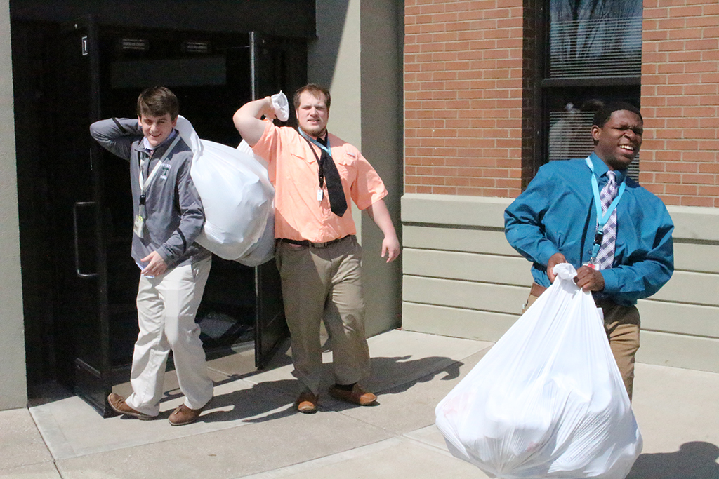 Bags of shoes are carried to the WaterStep truck Mar. 28.