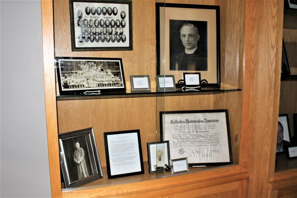 A collection of photos of Monsignor Alfred Steinhauser and other memorabilia can be found in a case in Alumni Hall.
