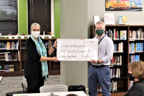 Trinity House and Activities Director Mr. Adam Klein presents a check for $6,400 to Sister Larraine Lauter, head of Water with Blessings.